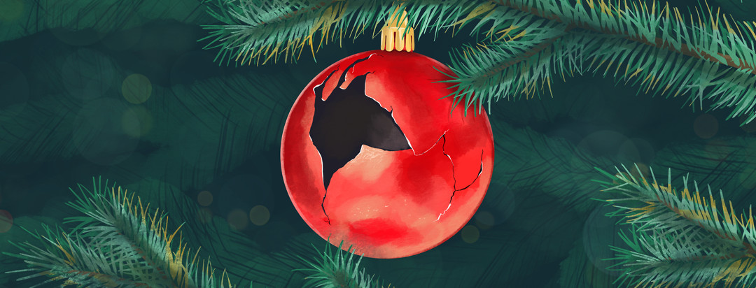 A cracked and broken ornament ball hanging on a Christmas tree.