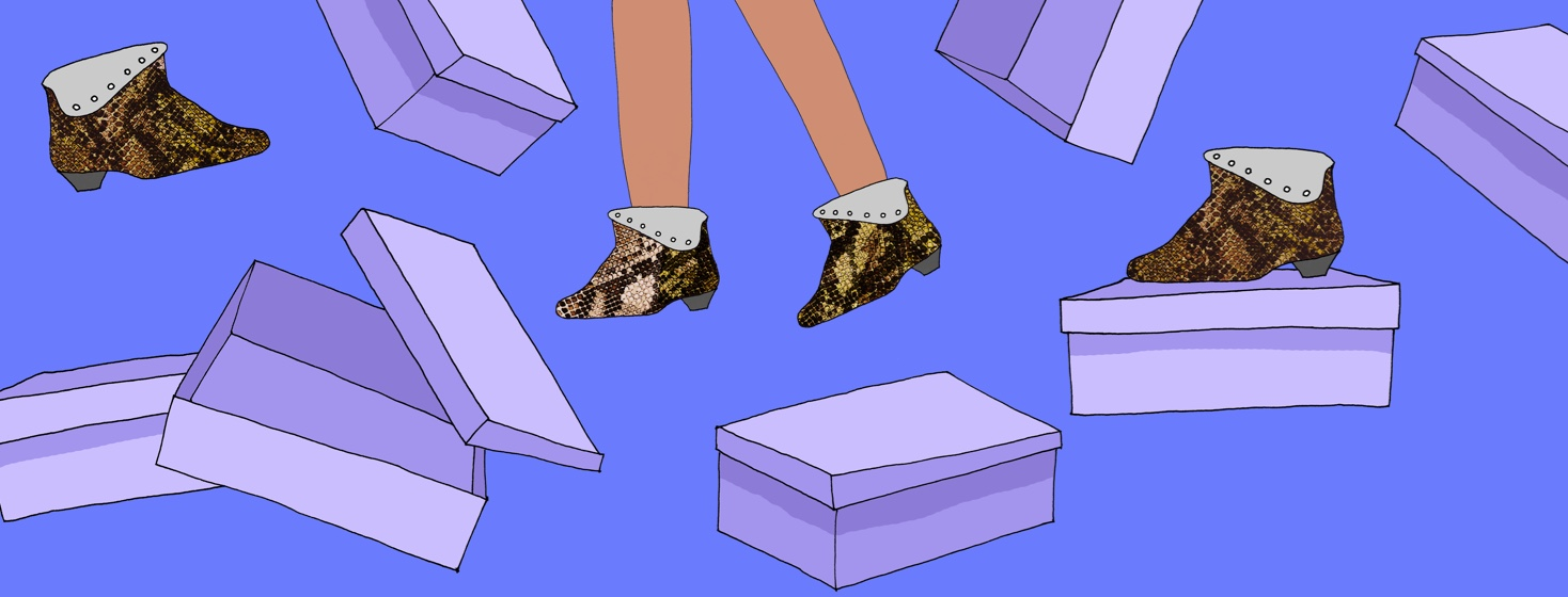 A set of legs wearing ankle height snake skin boots with open boxes scattered around them