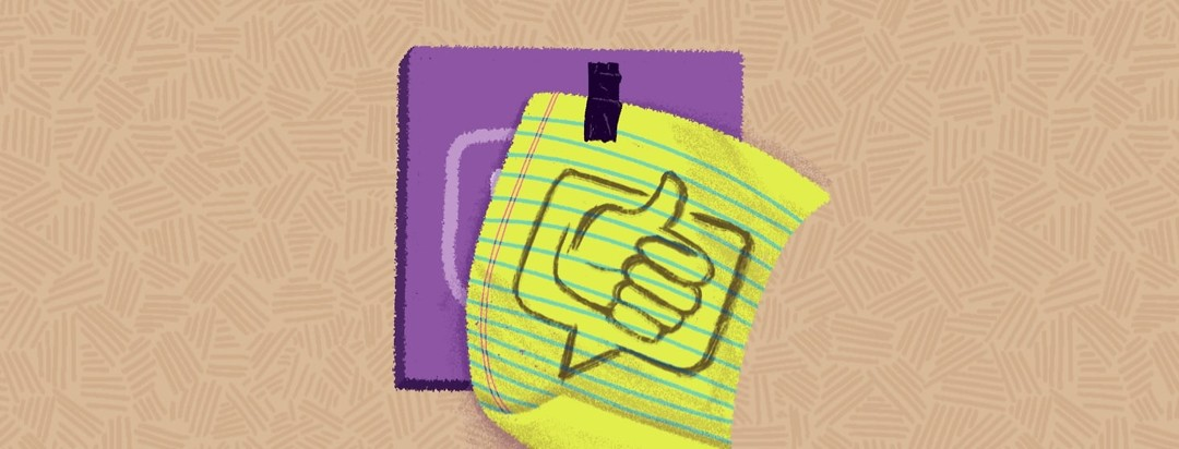 A yellow lined paper with a thumbs up and and a speech bubble quickly drawn on it is taped over a physical representation of the RA.net logo.