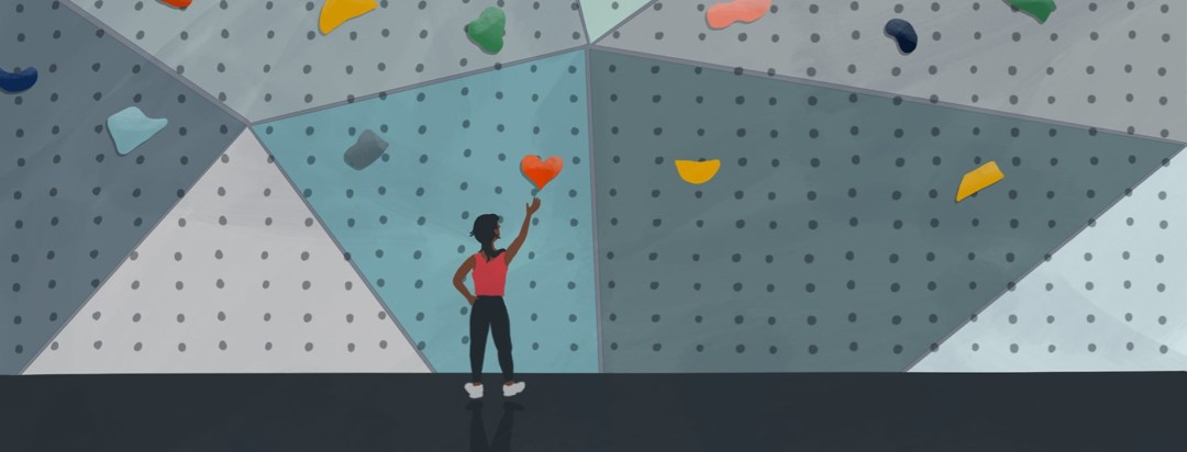 person on ground reaching for a heart shaped rock on a climbing wall