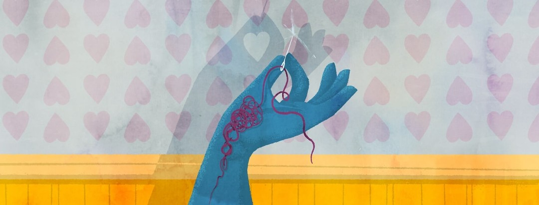 A hand holding a single sewing needle. In the shadow of the hand and needle cast on the wall is a heart.