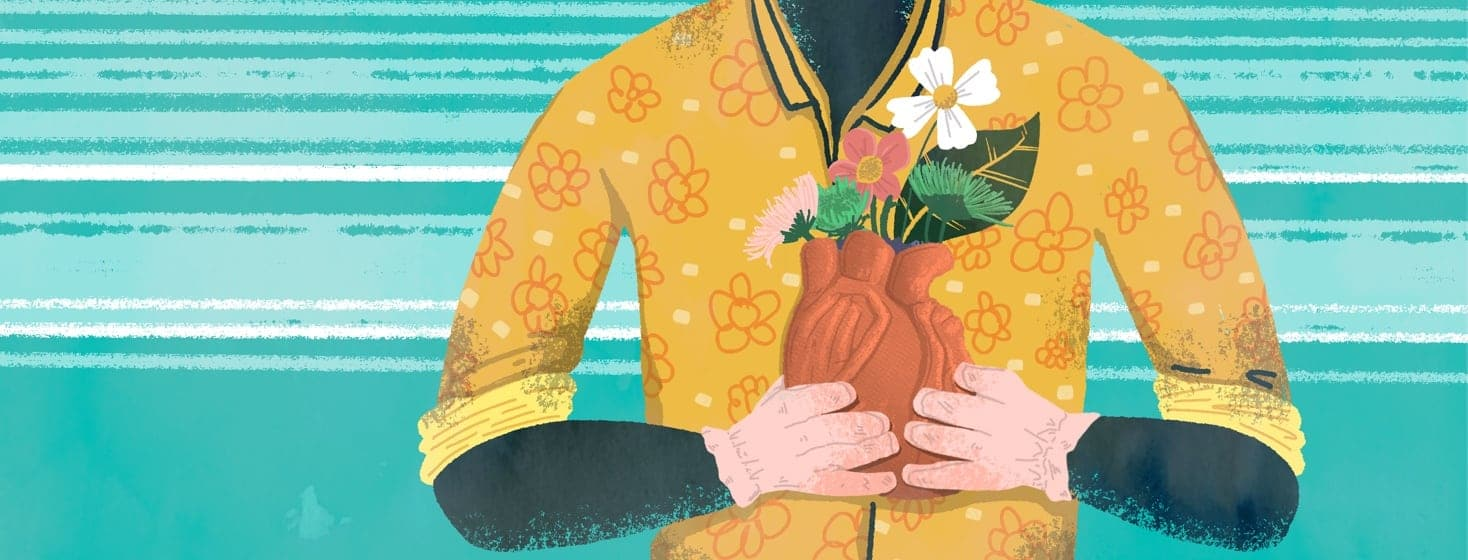 A person holding an anatomical heart shaped planter full of flowers.