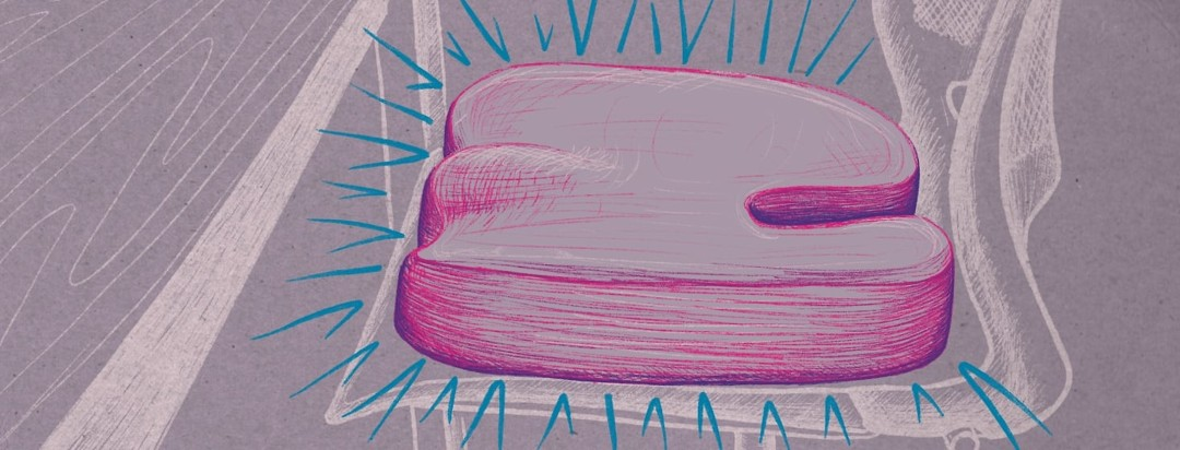 A glowing memory foam seat cushion sitting on a desk chair