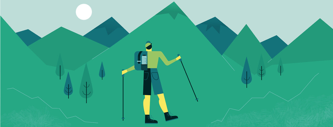 Man using trekking poles while hiking, surrounded by mountains and trees.